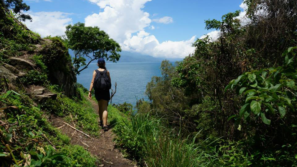 A student walks down a path during a research project abroad
