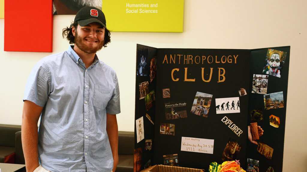 student standing in front of anthropology club poster